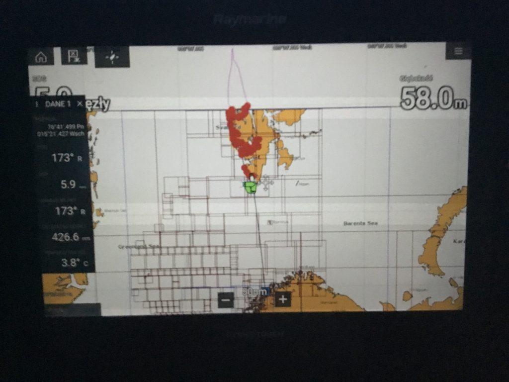 0800 Minęliśmy w niewielkiej odległości dwie jednostki rybackie, najprawdopodobniej rosyjskie trawlery. To chyba ostatni kontakt z cywilizacją na te najbliższe dni. Płyniemy na zrefowanym grocie oraz foku. Utrzymujemy średnią prędkość 6.5 węzła i czekamy na korzystniejszy kierunek wiatru, aby móc nieco przyspieszyć. 412 mil morskich do wybrzeży Norwegii. Już mam na sobie odzież termiczną, bluzę, puchówkę oraz pół sztormiaka. Kapitalna nadbudówka Azimuth'a zapewnia bardzo duży komfort. 0900 20 metrów od lewej burty wyłonił się na wieloryb, popatrzył i popłynął swoim kursem. Nie wzbudziliśmy jego zainteresowania, czego nie można powiedzieć o stadzie delfinów, które już od dłuższego czasu baraszkują przy jachcie. 1000 Stada delfinów podbijają stawkę, zaczynają seryjnie wyskakiwać ponad wodę. Pierwszy raz przez chmury przebiło się słońce, zapowiada się piękny dzień. W nocy istnieje szansa pojawienia się zorzy polarnej. Będziemy wypatrywać. A na razie obserwujemy coraz większe fale, koło 3 metrów. Nie wpływa to na razie na wybór Prezesa, a szkoda, bo alkohol w Norwegii drogi. Chyba muszę komuś kazać wyczyścić zęzę, albo przynajmniej usmażyć złapane wczoraj dorsze. 1200 Czyli południe. Leniwe południe. Właśnie skończyłem swoją 6-godzinną wachtę i zamierzam trochę poleniuchować. Wiatr odkręcił w stronę północy, a wraz z nim fala. Co ósma fala przelewa się przez pokład. Takie rzeczy na wachcie się liczy. Z tych ciekawszych spraw: poluzowała się uszczelka w okienku kuchennym i co każdy przechył wlewa się pół szklanki wody. Całe szczęście wstał Paweł i udało się zakleić z zewnątrz. W porcie naprawimy. 1600 Miałem cztery godziny odpoczynku. W tym czasie zjedliśmy na obiad przywiezione z Polski schabowe, delfiny co jakiś czas pojawiały się przy burcie, fala się wydłużyła i urosła. Mamy dobrą prędkość przelotową około 7 węzłów. Słońce nas nie rozpieszcza, ale co jakiś czas przebija się na chwilę przez chmury. Być może czeka nas spektakularny zachód słońca. Powoli morze zaczyna s